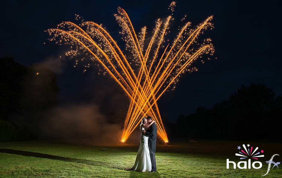 Wedding couple embracing with two fans of gold fireworks going off behind them. Photographer Paul Wilkinson
