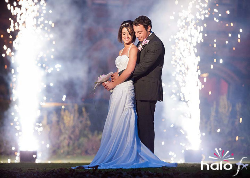 Bride and groom embracing posing for wedding album picture in from of two silver fountain fireworks