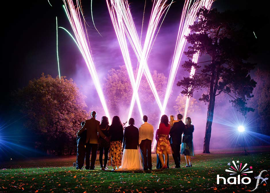 Laura and John with close family watching their wedding fireworks display with pink purple fireweorks