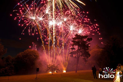 Wedding couple watching the red and gold glitter finale to their music and fireworks display