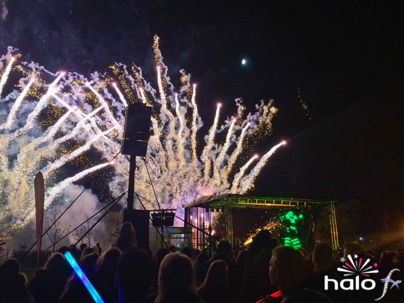 Two large silver peacock firework fan cakes behind the Glowbot on the main stage at the Rugby Roundtable Fireworks event