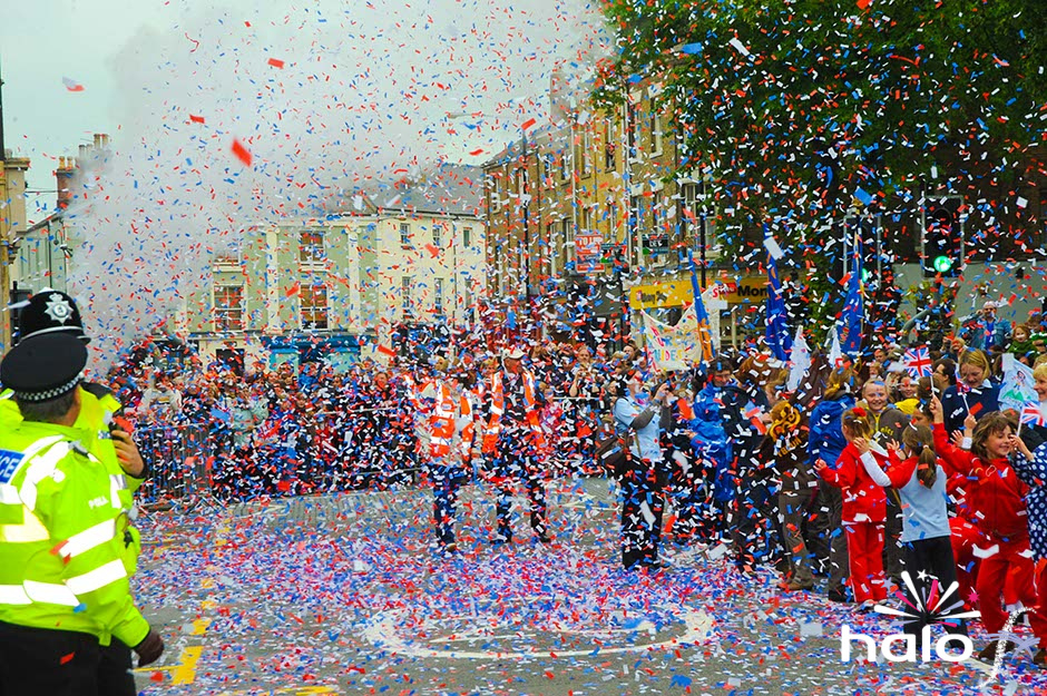 A heavy fall of red white and blue confetti falling over the crowd watching the parade