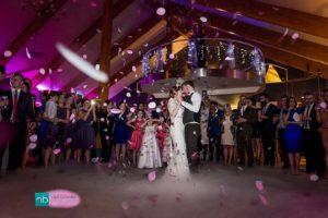 Bride and groom first dance with dry ice and a gentle fall of pink and white confetti petals