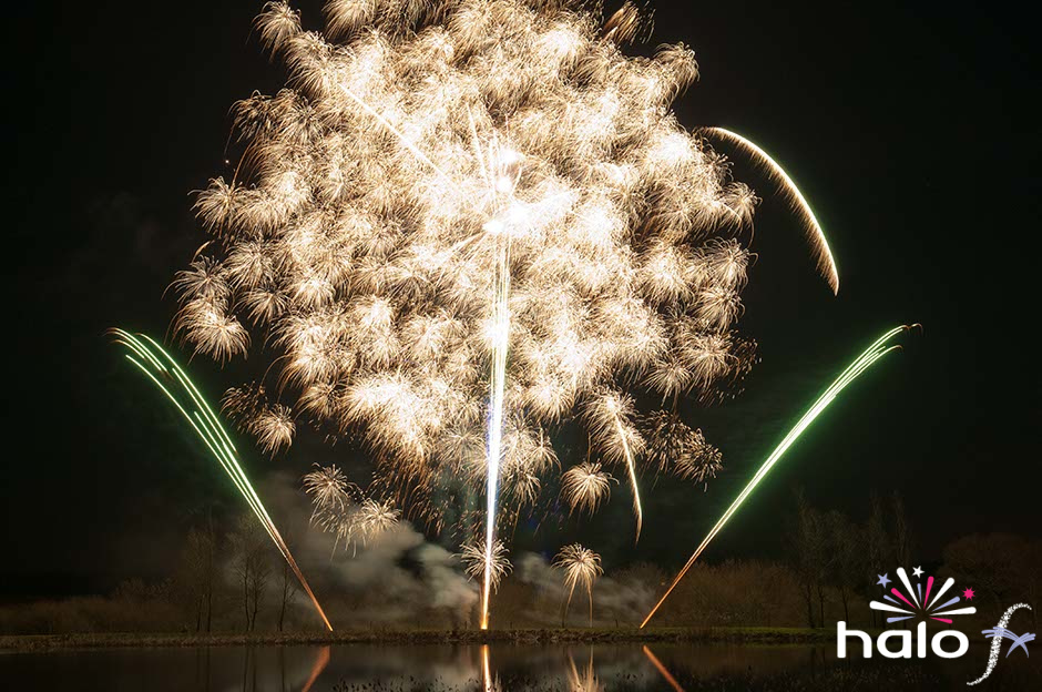 Large burst of crackling gold fireworks as part of a Scattering Ashes fireworks display next to a lake near Oxford