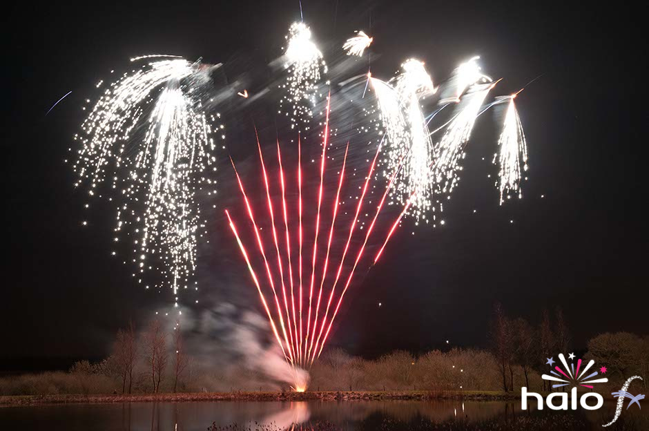 Stunning silver white falling lkeaves fireworks with red tail fans as part of a scattering ashes fireworks display next to a lake in Oxfordshire