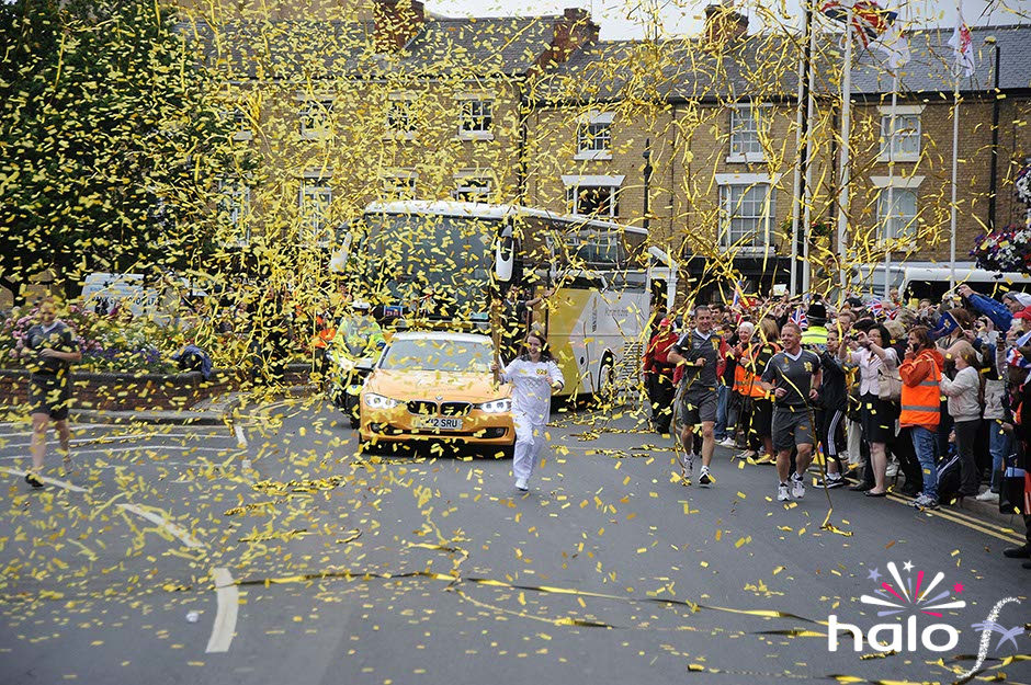 A heavy fall of gold streamers and confetti covering the Olympic Torch bearer as it passes Rugby School