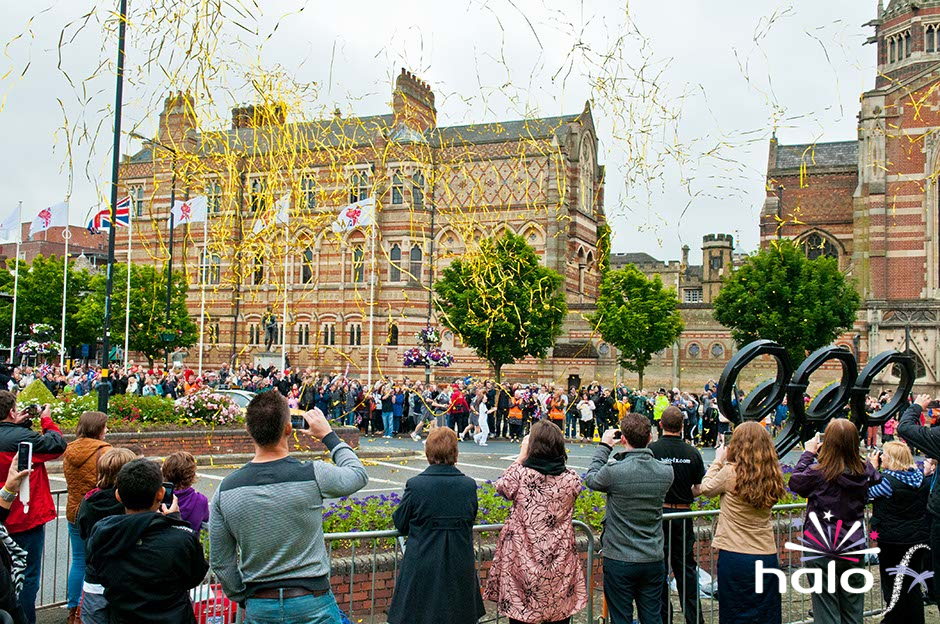 A large number of gold confetti streamers in the air as the Olympic Torch passes Rugby School