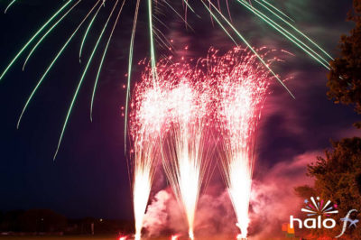 Three red glitter mines with a green shell bursting above as part a scattering ashes fireworks display in Cornwall
