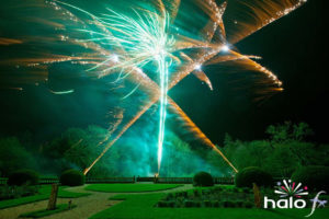 Crossing gold glitter with green fireworks in the centre as part of a scattering ashes fireworks display in Warwickshire
